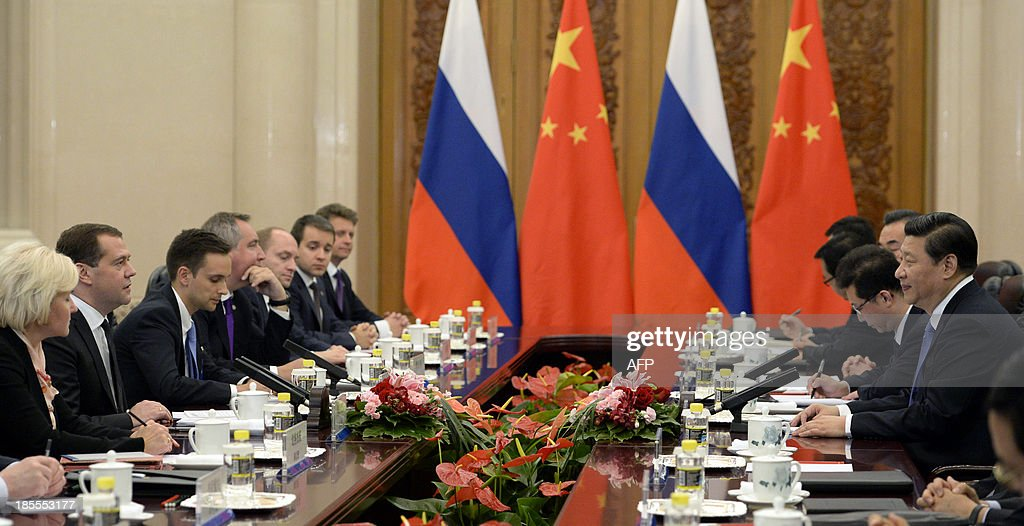 Russian Prime Minister Dmitry Medvedev (2nd L) talks with Chinese President Xi Jinping (R) during a meeting at the Great Hall of the People in Beijing on October 22, 2013.