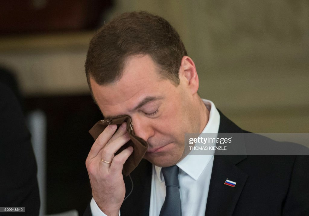 Russian Prime Minister Dmitry Medvedev wipes his eye during a breakfast with representatives of the German economy at the 52nd Munich Security Conference (MSC) in Munich, southern Germany, on February 13, 2016. / AFP / THOMAS KIENZLE