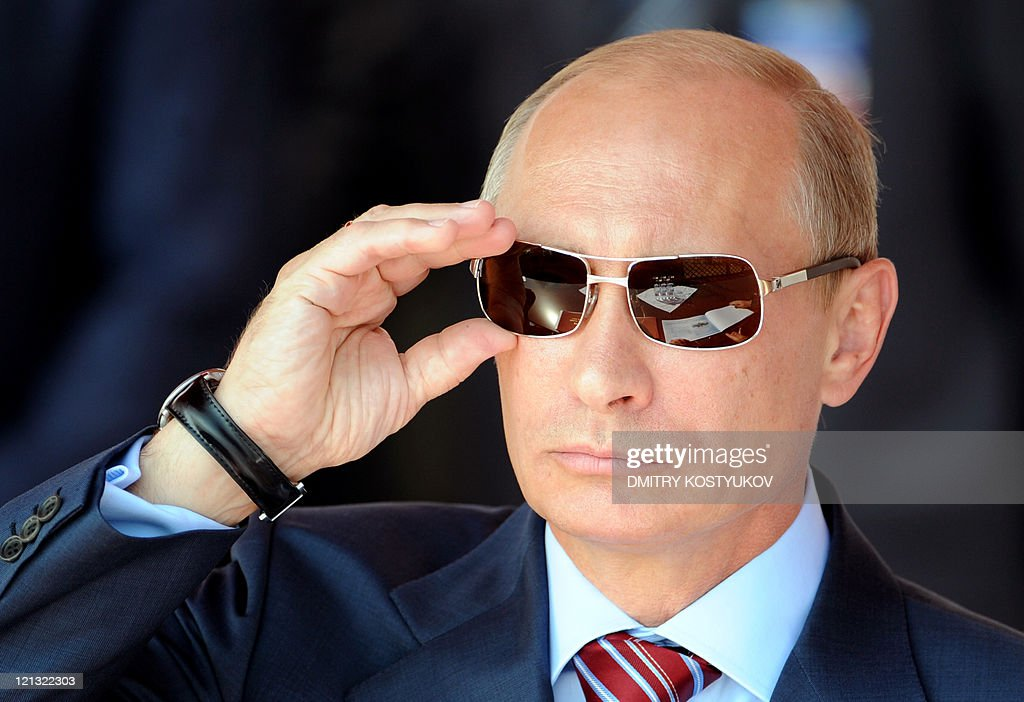 Russian Prime Minister <a gi-track='captionPersonalityLinkClicked' href=/galleries/search?phrase=Vladimir+Putin&family=editorial&specificpeople=154896 ng-click='$event.stopPropagation()'>Vladimir Putin</a> adjusts his sunglasses as he watches an air show during MAKS-2011, the International Aviation and Space Show, in Zhukovsky, outside Moscow, on August 17, 2011. AFP PHOTO / DMITRY KOSTYUKOV