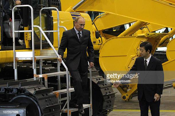 Russian Prime Minister Vladimir Putin is guided by Yasuhisa Tsukamoto Director General of the Komatsu Company in Russia while visiting the KMR plant...