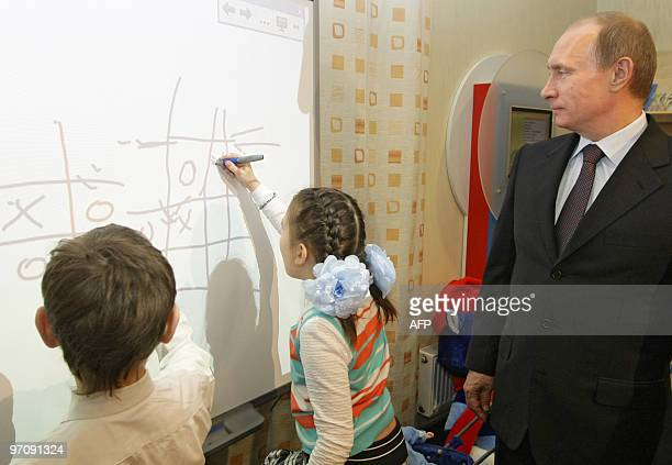 Russian Prime Minister Vladimir Putin plays a game of tictactoe with schoolchildren during a visit to a library in Tyumen on February 26 2010 Putin...