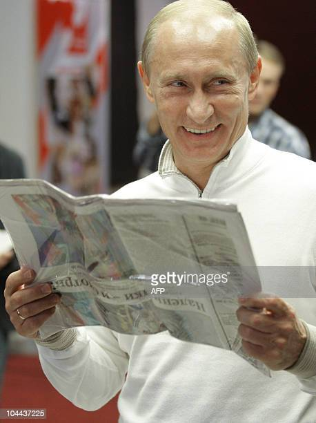 Russian Prime minister Vladimir Putin smiles while holding a news paper during a visit to the Baltic Media Group holding in StPetersburg on September...