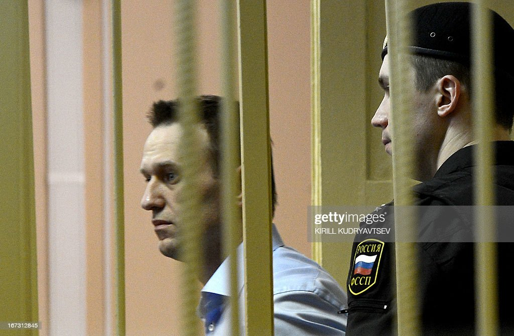 Russian protest leader Alexei Navalny walks past a guard as he attends a hearing of his case in a court in the provincial northern city of Kirov on April 24, 2013. Navalny went today on trial on charges that he says were ordered by President Vladimir Putin in revenge for him daring to oppose the Kremlin.