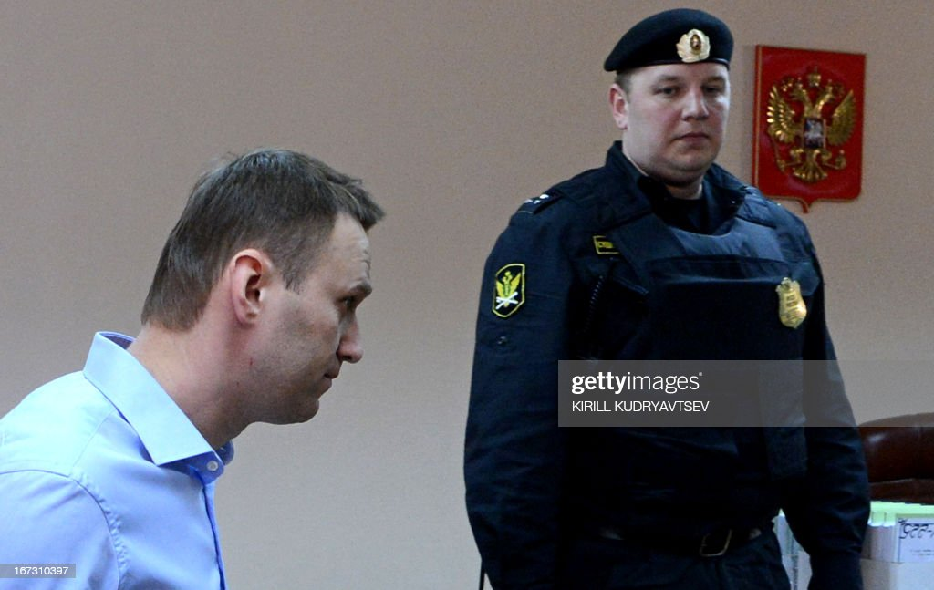 Russian protest leader Alexei Navalny walks past a guard in a court during in the provincial northern city of Kirov on April 24, 2013. Navalny went today on trial on charges that he says were ordered by President Vladimir Putin in revenge for him daring to oppose the Kremlin.