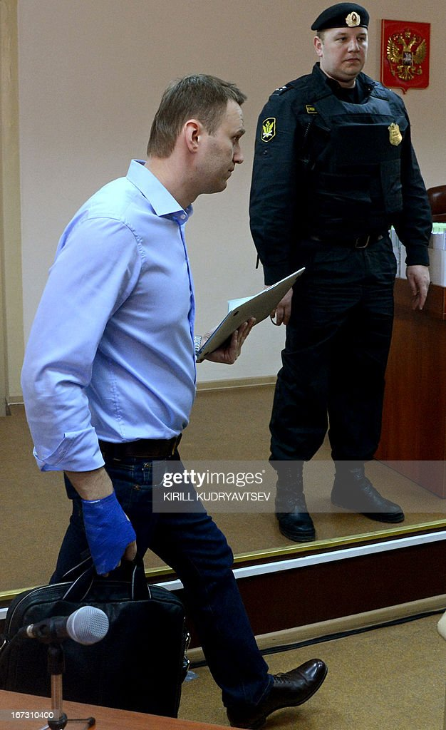 Russian protest leader Alexei Navalny walks past a guard in a court during in the provincial northern city of Kirov on April 24, 2013. Navalny went today on trial on charges that he says were ordered by President Vladimir Putin in revenge for him daring to oppose the Kremlin. AFP PHOTO/KIRILL KUDRYAVTSEV