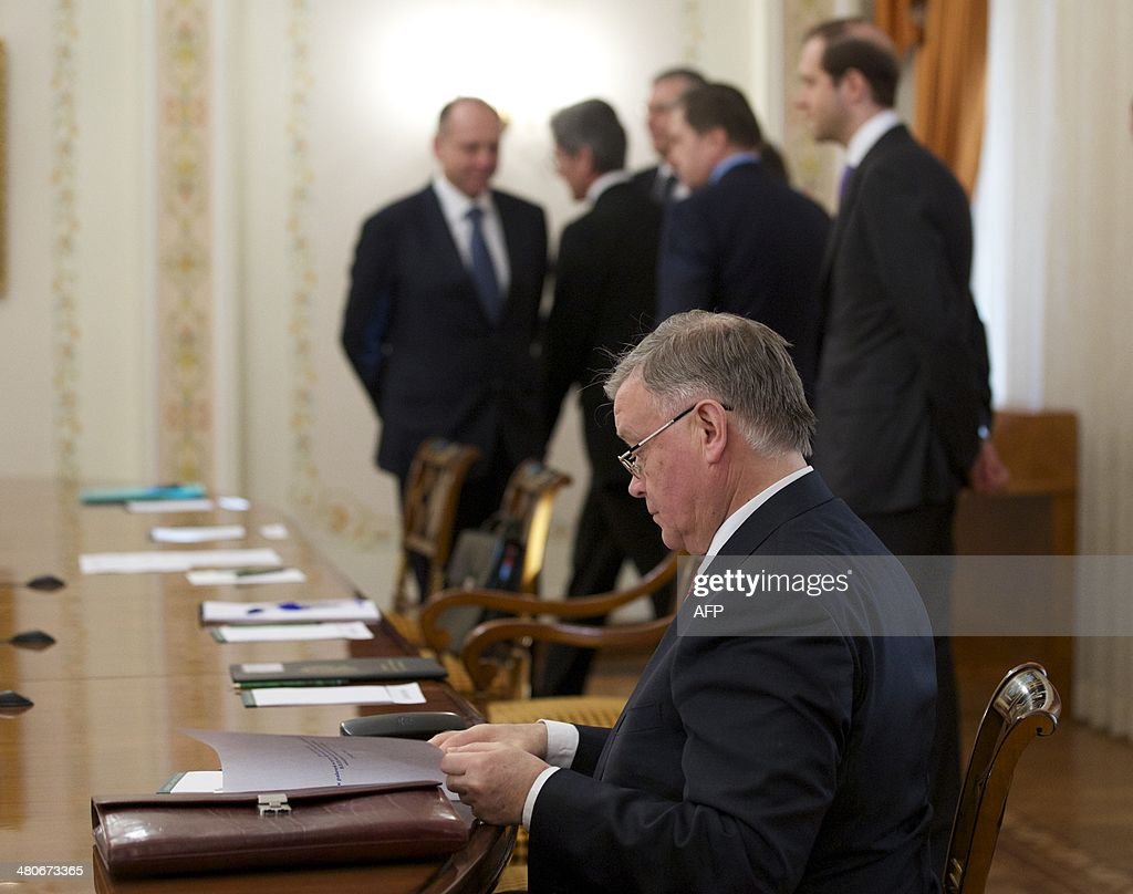 Russian Railways Chief Vladimir Yakunin (front) reads documents while waiting for Russia's President Vladimir Putin before his meeting with Siemens AG CEO Joe Kaeser in the Novo-Ogaryovo residence outside Moscow, on March 26, 2014. AFP PHOTO / POOL/ ALEXANDER ZEMLIANICHENKO