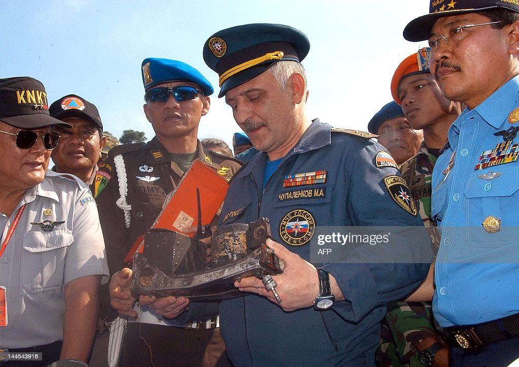 Russian rescue official Cupalenkov holds the recovered cockpit voice recorder of the Russian Sukhoi Superjet 100 while Indonesian officials Tatang...