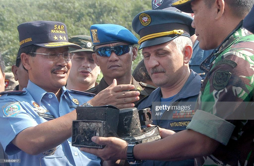 Russian rescue official Cupalenkov looks at the recovered cockpit voice recorder of the Russian Sukhoi Superjet 100 while Indonesian officials Vice...