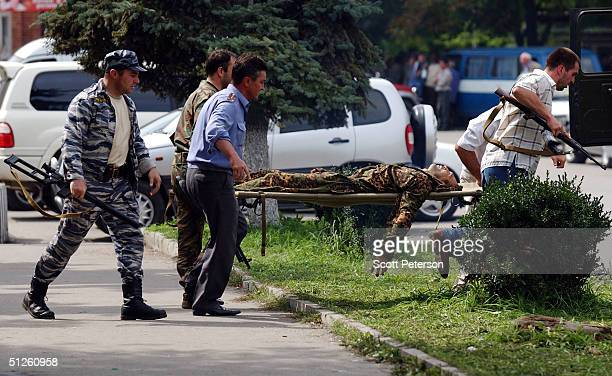 Russian rescue workers carry a soldiers on a stretcher near a school September 3 2004 in Beslan Russia More than 200 people were reportedly killed...
