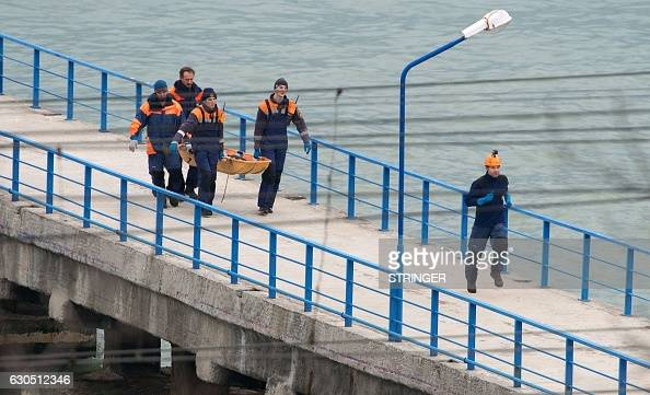Russian rescuers carry a stretcher with a body recovered after a Russian military plane crashed in the Black Sea on a pier outside Sochi on December...