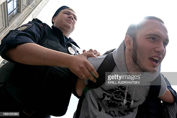 A Russian riot policeman detains a gay and LGBT rights activist during an unauthorized gay rights rally in cental Moscow on May 25 2013 AFP...