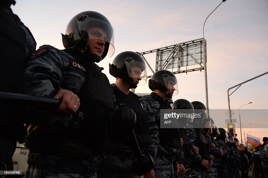 Russian riot policemen block a street during rally in Moscow's southern Biryulyovo district on October 13, 2013. Some 200 people have been arrested during the race riot in which nationalists outraged by a murder blamed on a migrant smashed shop windows and assaulted security guards. Demonstrators were outraged over the murder on Thursday of a 25-year-old local man named Yegor Shcherbakov. Police said he was stabbed by an unknown assailant in unclear circumstances while his fiancee -- identified only by her first name Ksenya -- watched.