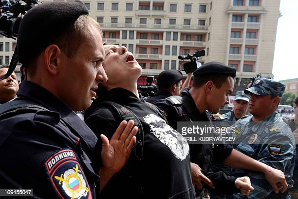 Russian riot policemen detain a gay and LGBT rights activist during unauthorized gay rights rally in cental Moscow on May 25 2013 AFP PHOTO/KIRILL...