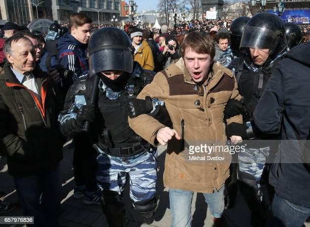 Russian riot policemen detain an opposition activist during an unsantioned protest rally in front of the Pushkin monument at Pushkinskaya Square...