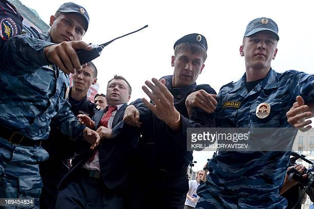 Russian riot policemen detain gay and LGBT rights activist Nikolai Alexeyev during an unauthorized gay rights rally in cental Moscow on May 25 2013...