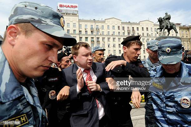Russian riot policemen detain gay and LGBT rights activist Nikolai Alexeyev during an unauthorized gay rights activists rally in central Moscow on...