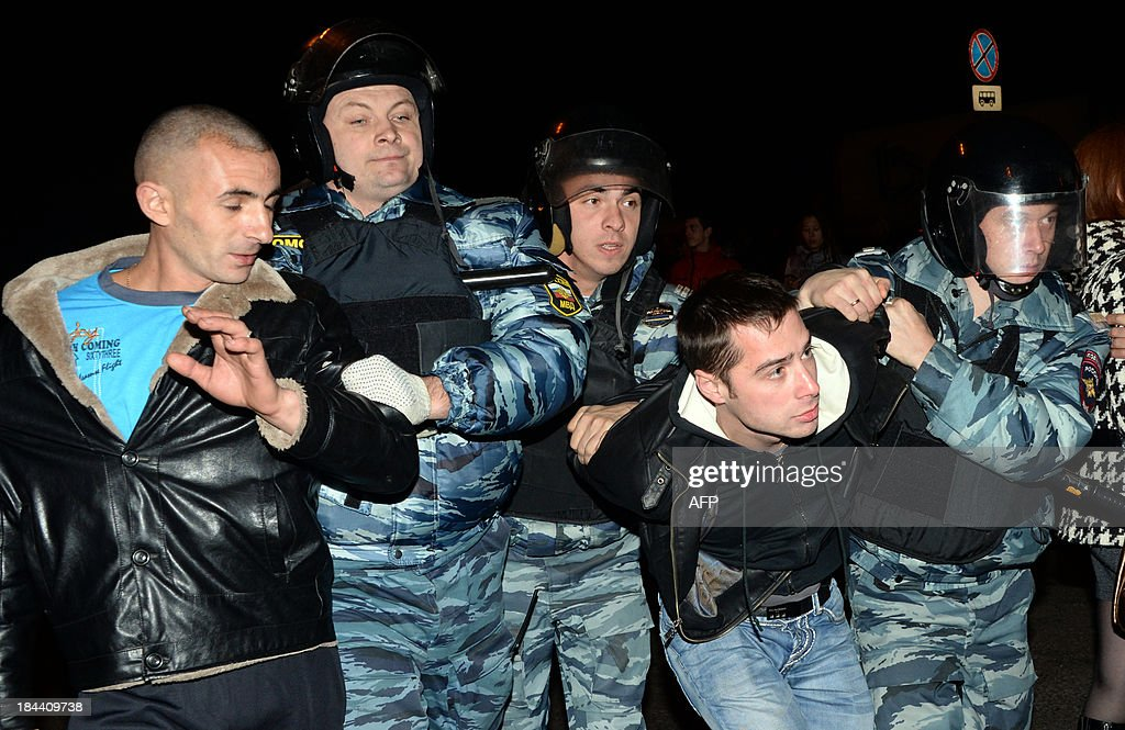 Russian riot policemen detain two men at the end of a rally in Moscow's southern Biryulyovo district on October 13, 2013. Some 200 people have been arrested during the race riot in which nationalists outraged by a murder blamed on a migrant smashed shop windows and assaulted security guards. Demonstrators were outraged over the murder on Thursday of a 25-year-old local man named Yegor Shcherbakov. Police said he was stabbed by an unknown assailant in unclear circumstances while his fiancee -- identified only by her first name Ksenya -- watched.