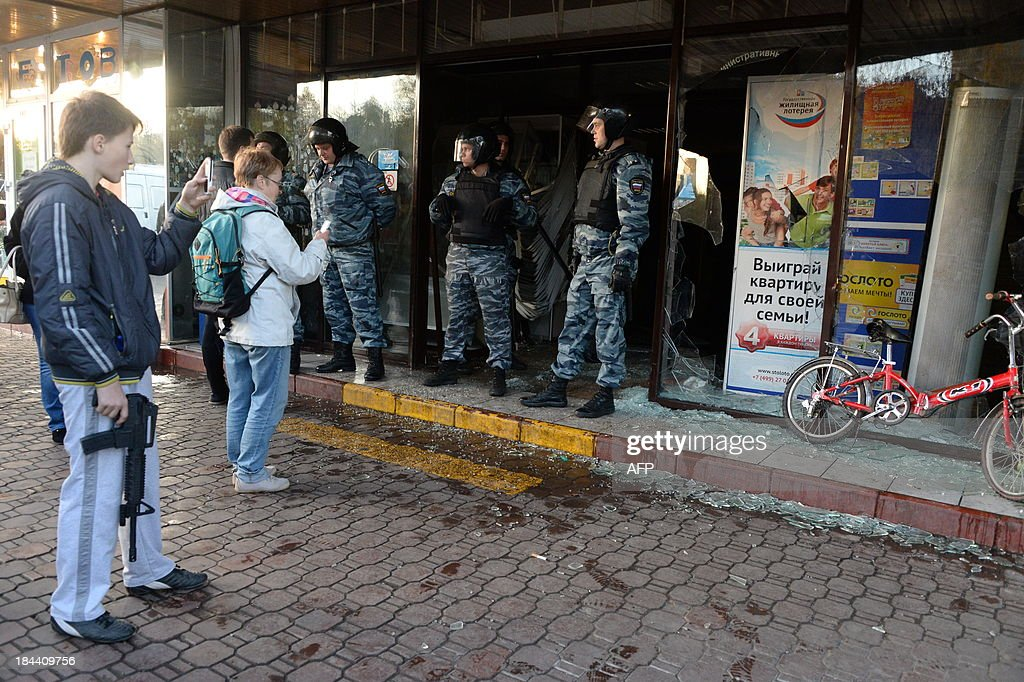 Russian riot policemen stand at a broken shop entrance during a rally in Moscow's southern Biryulyovo district on October 13, 2013. Some 200 people have been arrested during the race riot in which nationalists outraged by a murder blamed on a migrant smashed shop windows and assaulted security guards. Demonstrators were outraged over the murder on Thursday of a 25-year-old local man named Yegor Shcherbakov. Police said he was stabbed by an unknown assailant in unclear circumstances while his fiancee -- identified only by her first name Ksenya -- watched.