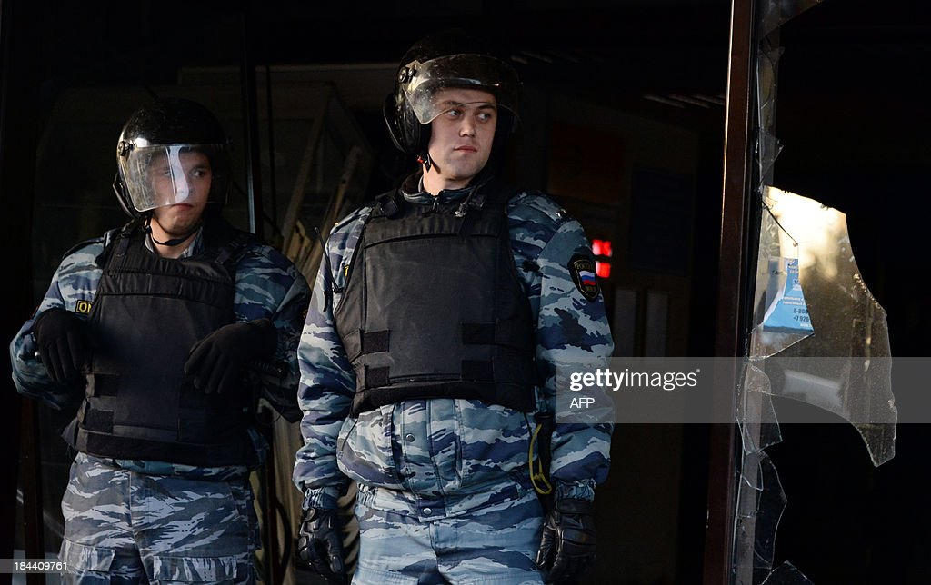 Russian riot policemen stand at a broken shop entrance during a rally in Moscow's southern Biryulyovo district on October 13, 2013. Some 200 people have been arrested during the race riot in which nationalists outraged by a murder blamed on a migrant smashed shop windows and assaulted security guards. Demonstrators were outraged over the murder on Thursday of a 25-year-old local man named Yegor Shcherbakov. Police said he was stabbed by an unknown assailant in unclear circumstances while his fiancee -- identified only by her first name Ksenya -- watched. AFP PHOTO / VASILY MAXIMOV