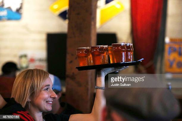 Russian River Brewing Company server carries a tray loaded with glasses of the newly released Pliny the Younger triple IPA beer on February 7 2014 in...