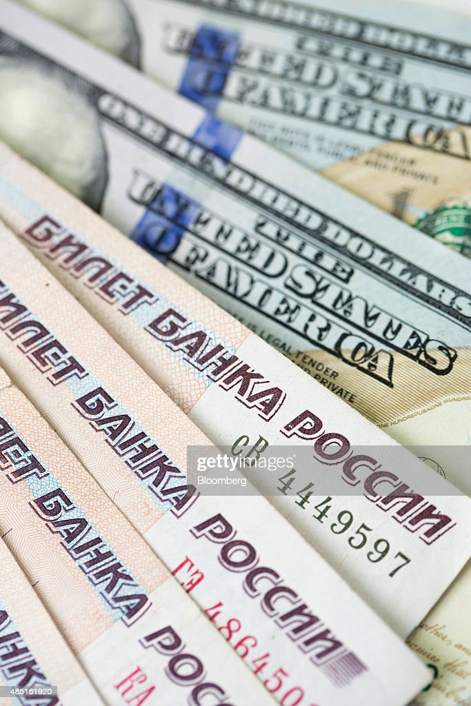 Russian Ruble notes sit on top of a pile of American Dollar bills in this arranged photograph in London, U.K., on Monday, Aug. 24, 2015. The plunge in the ruble is deepening divides within the free-trade project promoted by Russian President Vladimir Putin to bind former Soviet republics together. Photographer: Jason Alden/Bloomberg via Getty Images