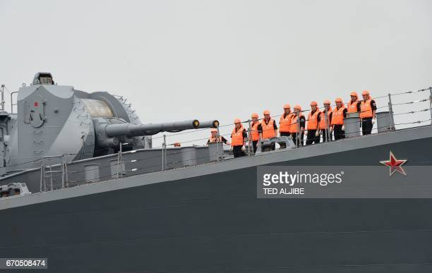 Russian sailors of the guidedmissile cruiser Varyag stand at the bow as the vessel arrives at the international port of Manila on April 20 2017 A...