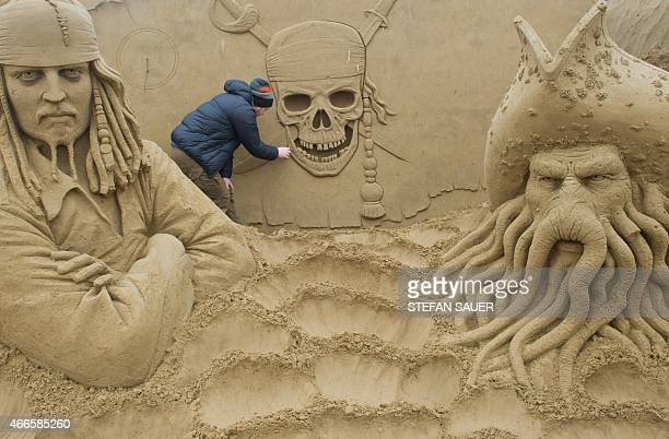 Russian sand sculptor Ivan Zverev carves a scene from the movie 'Pirates of the Caribbean' as preparations are under way for a sand sculpture...