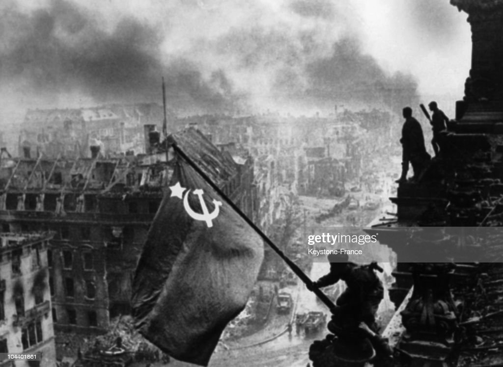 Russian sergeant KOVALIOV and another comrade raising the Russian flag onto the Reichstag while below them Berlin burns The real identity of these...