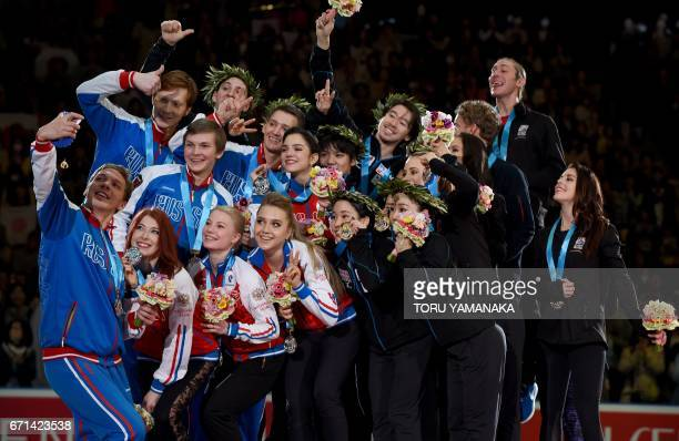 A Russian skater tries to take pictures of secondplaced teammates firstplaced Japan's skaters and thirdplaced US skaters during the awards ceremony...