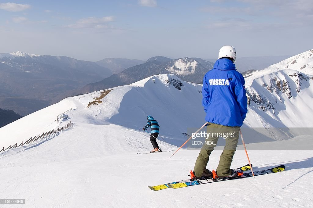 A Russian skier watches a woman set off from the peak of Mount Aigba in the 'Rosa Khutor' Extreme Park on February 11, 2013. With a year to go until the Sochi 2014 Winter Games, tests events and World Championship competitions are underway.