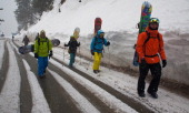 Russian skiers walk on a road with their snowboards at the world famous ski resort on February 20 2014 in Gulmarg 54 km to the west of Srinagar the...