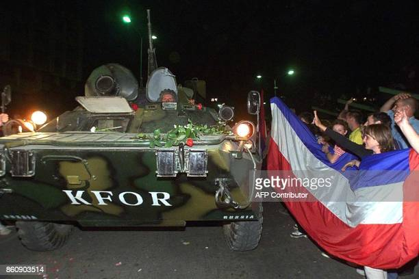 Russian soldiers enter Kosovo's capital of Pristina early 12 June 1999 greeted by the Serbs carrying Yugoslav flag several hours before NATO forces...