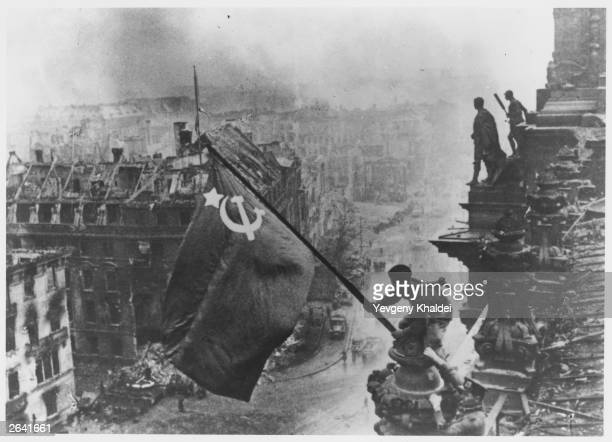 Russian soldiers flying the Red Flag made from table cloths over the ruins of the Reichstag in Berlin