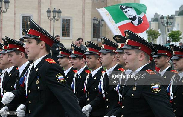 Russian soldiers march past a flag with a stylized portrait of Chechen President Ramzn Kadyrov during Victory Day celebrations in Grozny on May 9...