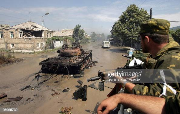 Russian soldiers ride an APC past a burntout Georgian tank in the South Ossetia town of Tskhinvali on August 11 2008 Britain's Europe Minister Jim...