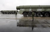 Russian soldiers stand next to truckmounted TopolM intercontinental ballistic missiles stand ready for rehearsals for the Victory Day parade at a...