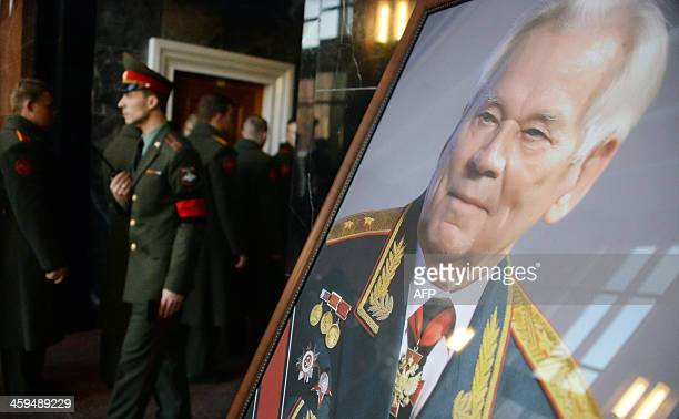 Russian soldiers walk past a portrait of Mikhail Kalashnikov the designer of the iconic AK47 assault rifle that was the favoured weapon of guerrillas...