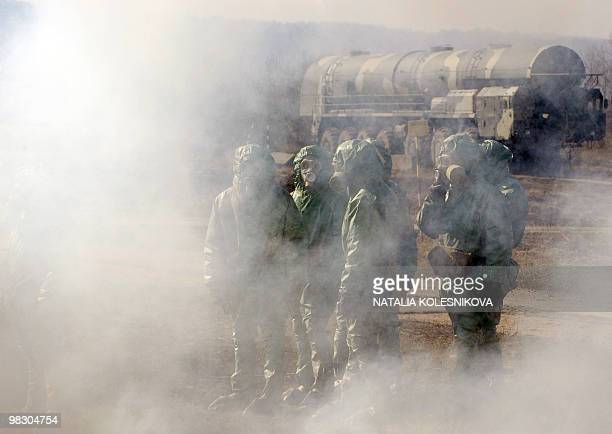Russian soldiers wear chemical protection suits as they stand next to model of Russian Topol intercontinental ballistic missile during a training...