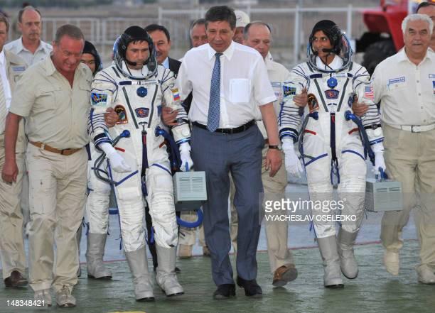 Russian space agency chief Vladimir Popovkin escorts astronauts Yuri Malenchenko of Russia and Sunita Williams of the US before boarding the Soyuz...