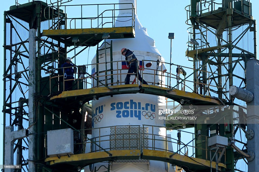 A Russian space agency employee wallks past the nose cone of Soyuz-FG launch vehicle with Soyuz TMA-11M spacecraft of the International Space Station (ISS) Expedition 39 aboard rising at a launch pad in the Russian-leased Baikonur cosmodrome in Kazakhstan, on November 5, 2013. The Soyuz TMA-11M with an international crew, including Japanese astronaut Koichi Wakata, Russian cosmonaut Mikhail Tyurin and US astronaut Rick Mastracchio, and with an unlit torch of Sochi 2014 Winter Olympic aboard is scheduled to blast off to the ISS from Baikonur on November 7. The torch is scheduled to return back to Earth on November 11.