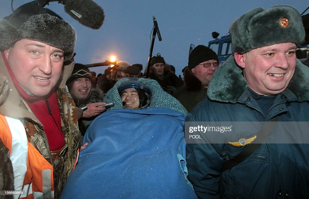 Russian space agency rescuers carry a crew member of the International Space Station (ISS), Japanese astronaut Akihiko Hoshide, shortly after his landing in Soyuz capsule near the town of Arkalyk in northern Kazakhstan, early on November 19, 2012. Russian cosmonaut Yury Malenchenko and two astronauts, Sunita Williams of the US and Akihiko Hoshide of Japan, touched down early today on the steppes of Kazakhstan in a Russian Soyuz capsule after spending over four months aboard the International Space Station (ISS).