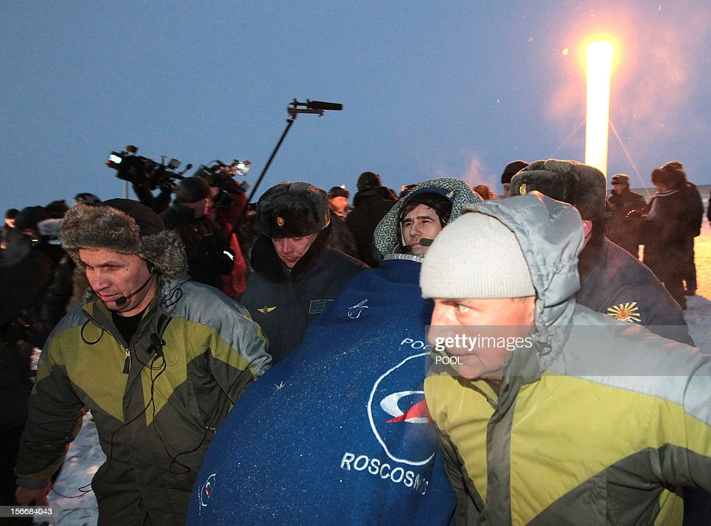 Russian space agency rescuers carry a crew member of the International Space Station (ISS), Russian cosmonaut Yury Malenchenko , shortly after his landing in Soyuz capsule near the town of Arkalyk in northern Kazakhstan, early on November 19, 2012. Russian cosmonaut Yury Malenchenko and two astronauts, Sunita Williams of the US and Akihiko Hoshide of Japan, touched down early today on the steppes of Kazakhstan in a Russian Soyuz capsule after spending over four months aboard the International Space Station (ISS). AFP PHOTO / POOL /MAXIM SHIPENKOV