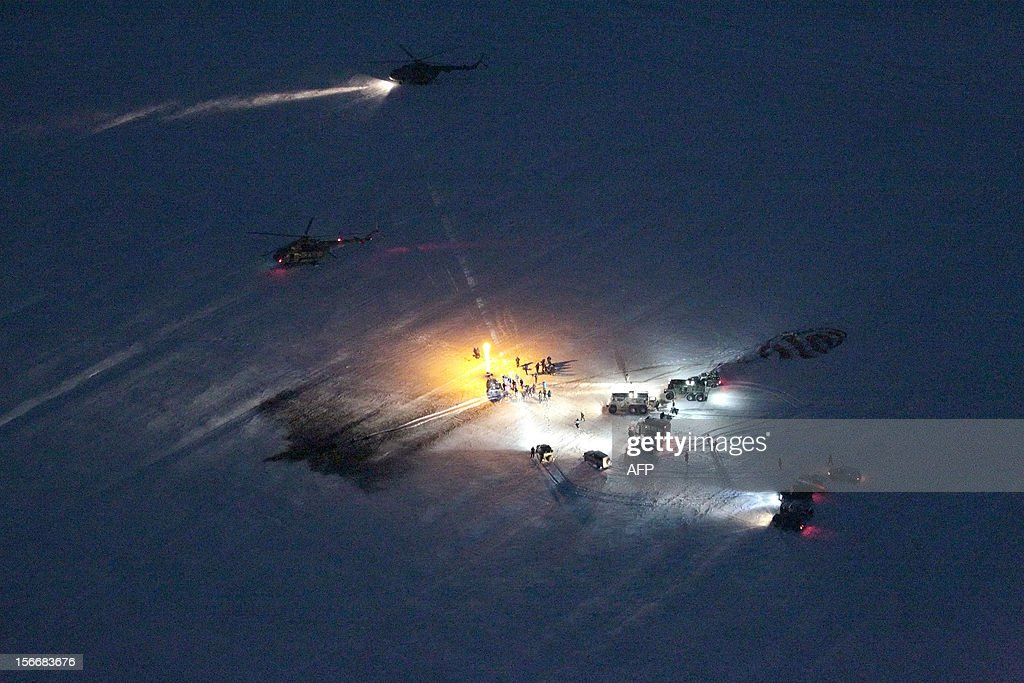 Russian space agency rescuers' helicopters and vehicles stand near the Soyuz capsule after the spacecraft 's landing near the town of Arkalyk in northern Kazakhstan, early on November 19, 2012. Russian cosmonaut Yury Malenchenko and two astronauts, Sunita Williams of the US and Akihiko Hoshide of Japan, touched down early today on the steppes of Kazakhstan in a Russian Soyuz capsule after spending over four months aboard the International Space Station (ISS).
