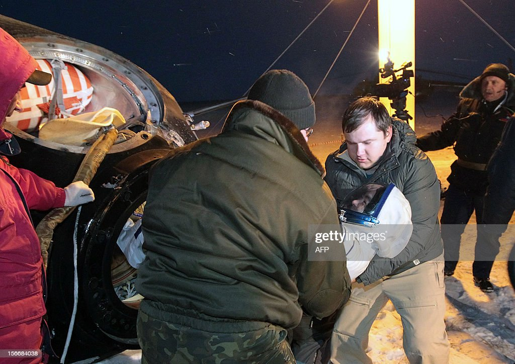 Russian space agency rescuers help a crew member of the International Space Station (ISS), Japanese astronaut Akihiko Hoshide, to get off a Soyuz capsule shortly after the spacecraft's landing near the town of Arkalyk in northern Kazakhstan, early on November 19, 2012. Russian cosmonaut Yury Malenchenko and two astronauts, Sunita Williams of the US and Akihiko Hoshide of Japan, touched down early today on the steppes of Kazakhstan in a Russian Soyuz capsule after spending over four months aboard the International Space Station (ISS).