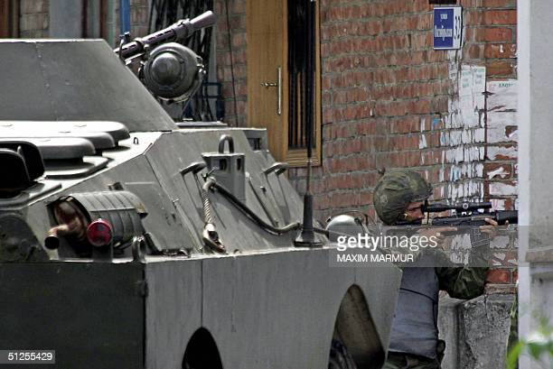 Russian special forces soldier aims at a position outside the school where a group of gunmen wearing belts laden with explosives are holding hostage...