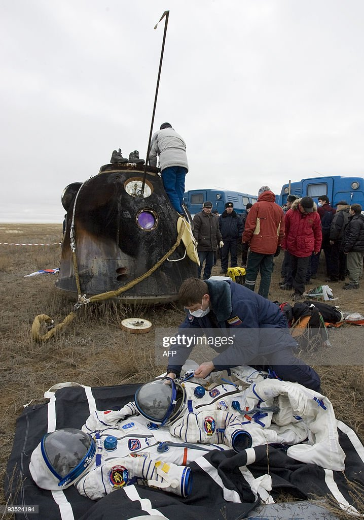 A Russian specialsit checks space suits in front of the Soyuz space capsule of the International Space Station crew of European Space Agency (ESA) astronaut Frank De Winne of Belgium, Russian cosmonaut Roman Romanenko and Canadian astronaut Robert Thirsk after landing in the steppe near the town of Arkalyk, in northern Kazakhstan on December 1, 2009.