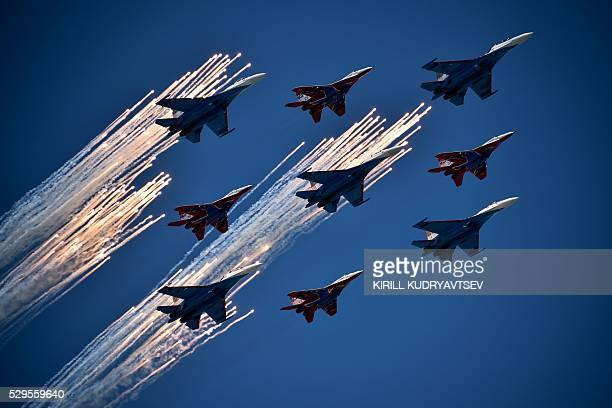 TOPSHOT Russian Su27 jet fighters and MIG 29 jet fighters fly over Red Square during the Victory Day military parade in Moscow on May 9 2016 Russia...