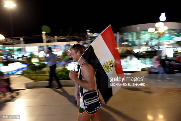 A Russian tourist carries an Egyptian flag in Sharm elSheikh on November 7 2015 Britain moved to repatriate thousands of tourists from Egypt's Sharm...