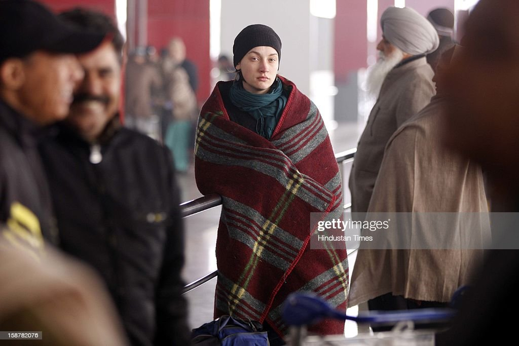A Russian tourist Sweta who is waiting for her flight to Goa take precautions against the Cold and foggy Weather at Indira Gandhi International Airporton December 28, 2012 in New Delhi, India. While the maximum temperature was recorded at 19 deg C, up from yesterday's temperature by 2.4 degrees, the minimum temperature today dipped to 6.3 deg C, a degree below the normal.