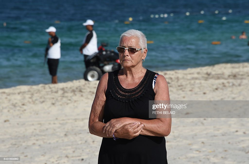 A Russian tourist walks past Tunisian security in the Marhaba Beach in Port el-Kantaoui, on the outskirts of Sousse south of the capital Tunis on June 26, 2016, on the first anniversary of an attack by a jihadist gunman in which 38 people were killed. Tourists fled in horror on June 26, 2015 as a Tunisian gunman pulled a Kalashnikov rifle from inside a furled beach umbrella and went on a shooting spree outside the five-star hotel. / AFP / FETHI